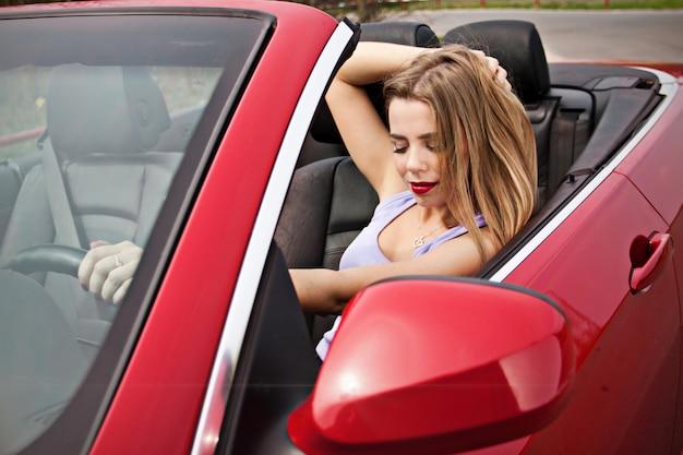 Pretty young girl in red cabrio