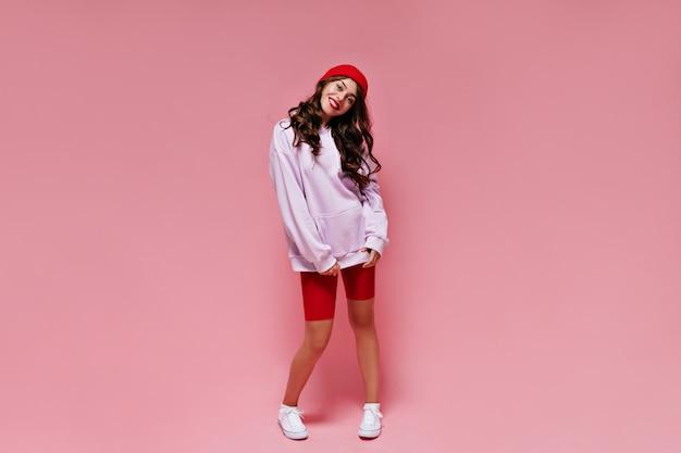 Bella ragazza in pantaloncini da ciclismo rossi e felpa con cappuccio oversize viola sorride sinceramente