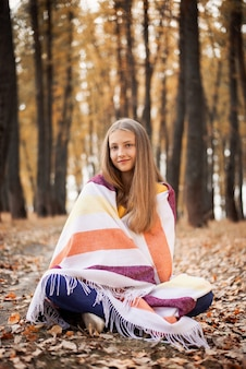 가 숲에서 노란 잎으로 덮여 바닥에 앉아 꽤 어린 소녀. 다채로운 우기, 자연에서의 자유 시간.