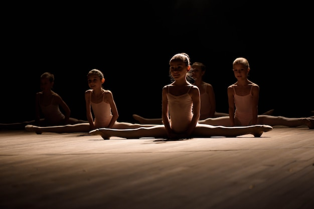 Pretty young girl sitting on stage having stretching and training for ballet dances.