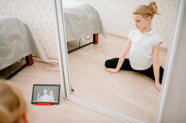 Pretty young girl in sportswear watching online video on laptop and doing fitness exercises at home.