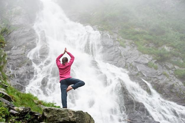 大きな強力な滝の近くのヨガのポーズで立っているかなり若い女の子。野生の穏やかな自然の中で瞑想する美しい女性