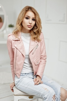 Pretty young girl in stylish pink leather jacket in white room