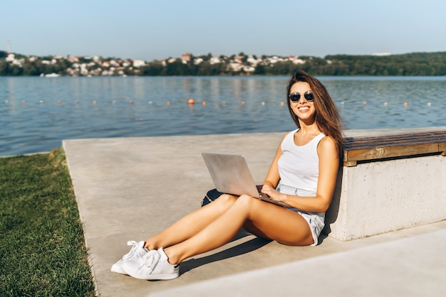 Pretty young girl using laptop outdoor in the city park.