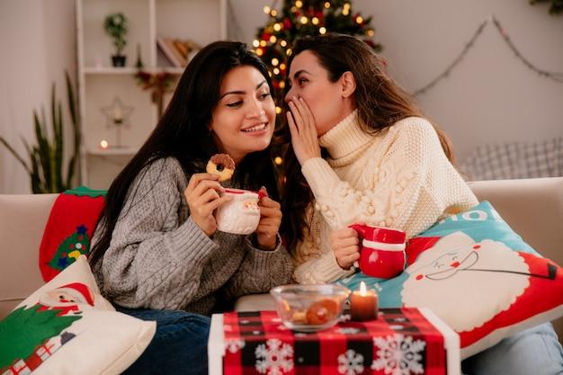 Bella ragazza sussurra nel suo orecchio amico seduto sulle poltrone e godersi il periodo natalizio a casa