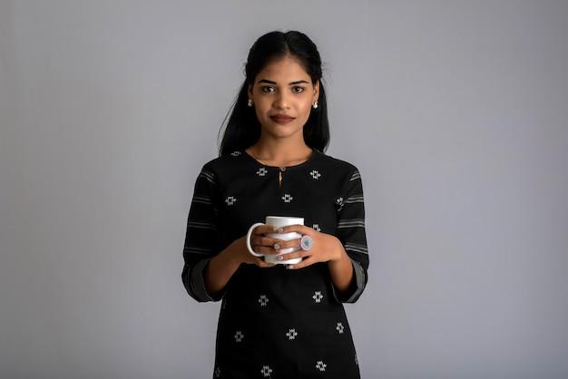 Довольно молодая девушка с чашкой чая или кофе позирует на сером фоне