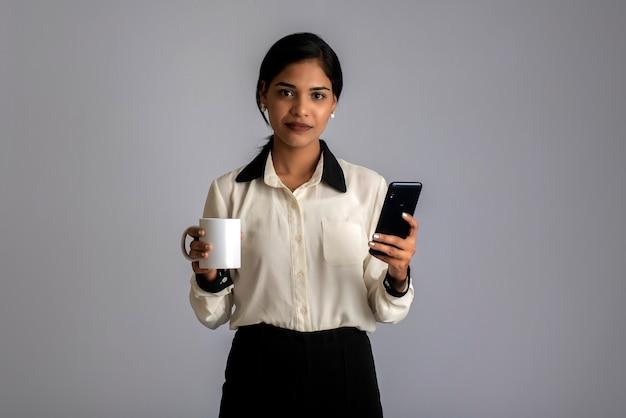 灰色でポーズをとってスマートフォンを使用してお茶やコーヒーのカップを持つかわいい少女。