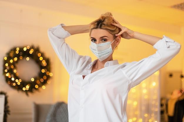 흰 셔츠에 보호용 의료 마스크를 쓴 예쁜 소녀가 방의 크리스마스 장식과 노란색 조명 배경에서 머리를 하고 있습니다. covid-19 개념과 여성의 아름다움