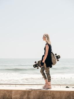 海岸沿いを歩いている手にスケートボードを持つかわいい少女。彼女の髪を吹く風。自由を楽しむ。