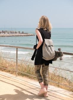 海岸沿いを歩いている手にスケートボードを持つかわいい少女