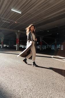 장화를 신고 세련된 긴 코트를 입은 곱슬머리를 한 예쁜 소녀가 주차장의 거리를 걷고 있습니다. 스트리트 페미닌한 스타일과 패션