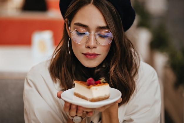 Симпатичная молодая девушка с темной волнистой прической, современным макияжем, стильными серьгами и бежевым плащом сидит на террасе городского кафе и держит в руках кусок чизкейка