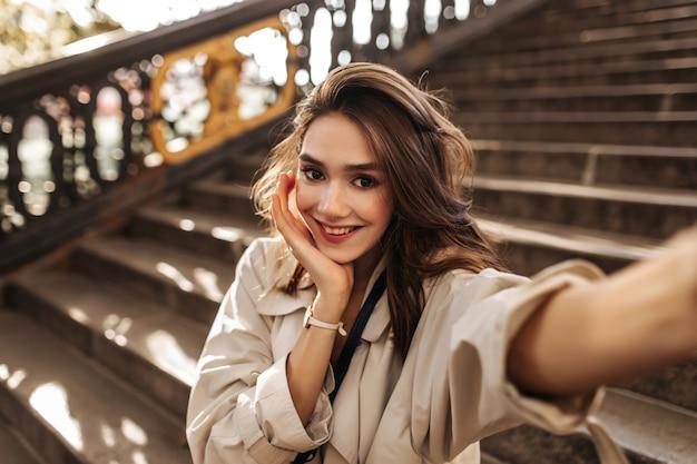 푹신한 갈색 머리, 붉은 입술, 세련된 트렌치 코트를 입고 웃고 있는 예쁜 소녀, 따뜻한 가을 도시에서 포즈를 취하고 낮에는 셀카를 찍는다