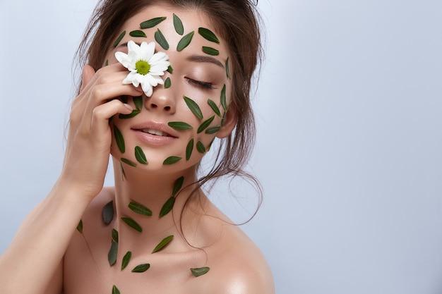 회색에 고립 된 그녀의 눈에 카밀레를 들고 몸에 녹색 잎을 가진 아주 어린 소녀