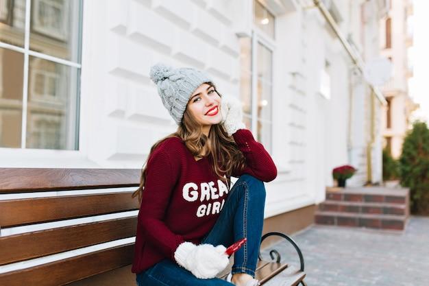 Довольно молодая девушка с длинными волосами в зимней шапке, джинсах и белых перчатках, сидя на скамейке на улице. она держит карамельно-красное сердце, улыбаясь.