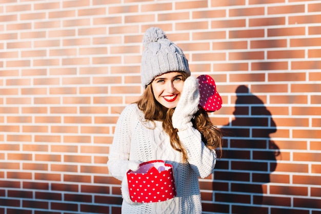 Pretty young girl with long hair in knitted hat and gloves on wall  outside. she holds open present in hands, smiling .