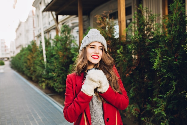 Pretty young girl with long hair in red coat and knitted hat walking on wooden house  . she holds coffee to go in white gloves, smiling friendly to side.