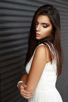 Довольно молодая девушка с макияжем в белом платье возле металлической темной стены