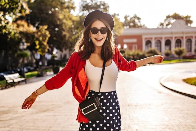 Ragazza graziosa con pelle pallida, capelli scuri, berretto francese, occhiali da sole in gonna a pois, top bianco e camicia rossa che cammina per la città soleggiata e ride