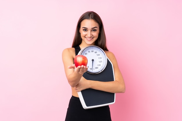 Pretty young girl with weighing machine over isolated pink  holding weighing machine and offering an apple