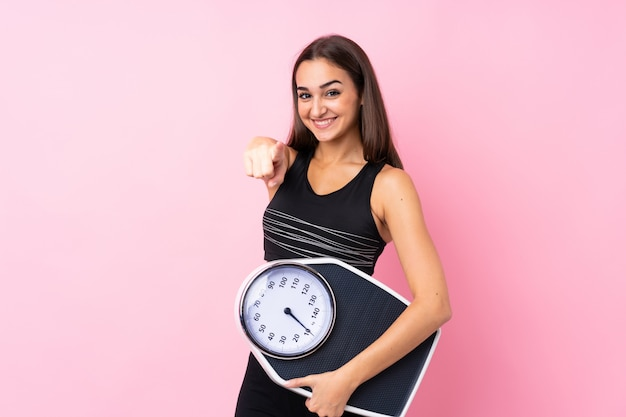Pretty young girl with weighing machine over isolated pink  holding a weighing machine and pointing to the front