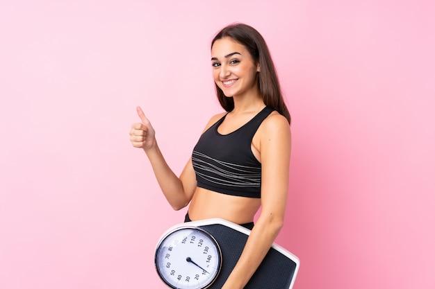 親指で計量機を保持している分離のピンクの上に計量機を持つかなり若い女の子