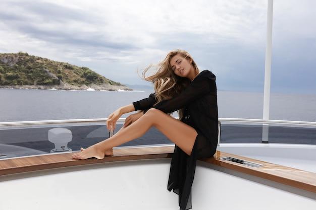 Bella ragazza sullo yacht, ama scalare montagne, volare in elicottero, in un bel vestito, donna sorridente e ridente vicino al mare, persona allegra e felice, vista incredibile, audace e libera