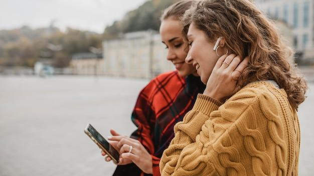 Ragazze abbastanza giovani che controllano insieme un telefono