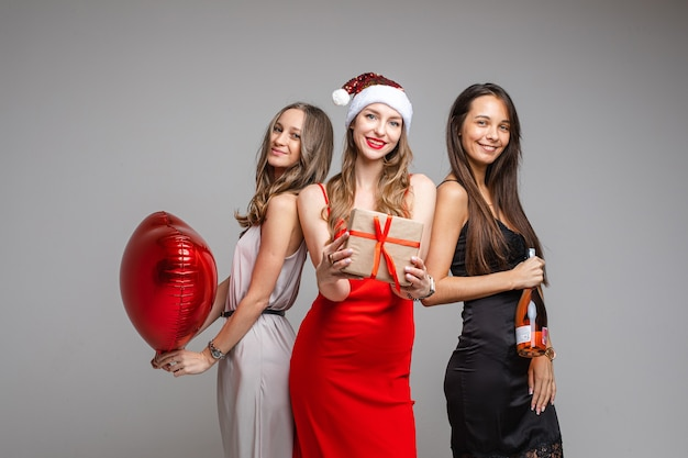 Pretty young girls friends in festive dresses holding gift, red balloon, champagne celebrating holiday on gray backdrop