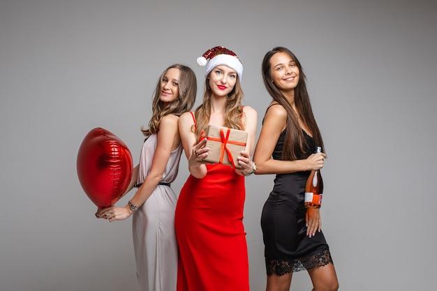 Довольно молодые девушки-друзья в праздничных платьях держат подарок, красный шар, шампанское, празднуют праздник на сером фоне