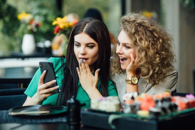 かなり若い女の子、テーブルの上に寿司プレートを置いて携帯電話を見ているパートナー。モダンなレストランテラス。友情の概念。