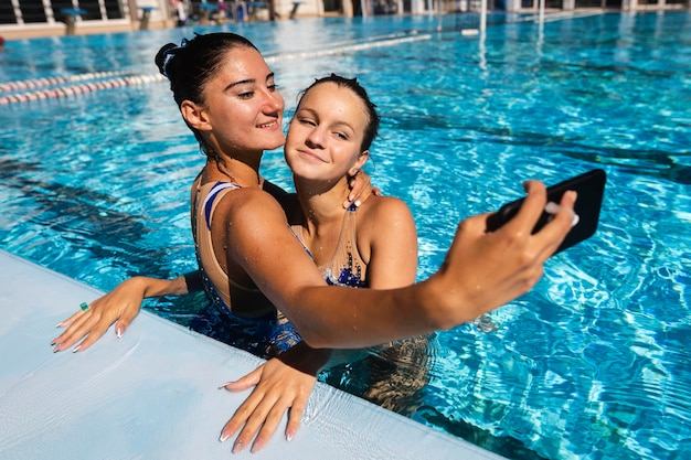 Pretty young girls taking a selfie at the pool