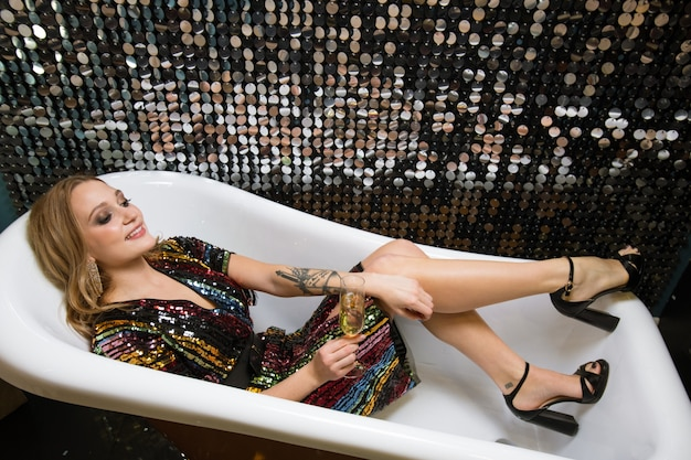 Pretty young glamorous woman cheering up with flute of champagne while lying in empty bathtub while enjoying party