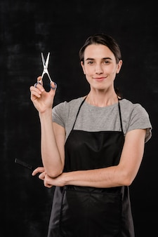Pretty young hairdresser in apron holding sharp scissors while standing in front of camera against black background