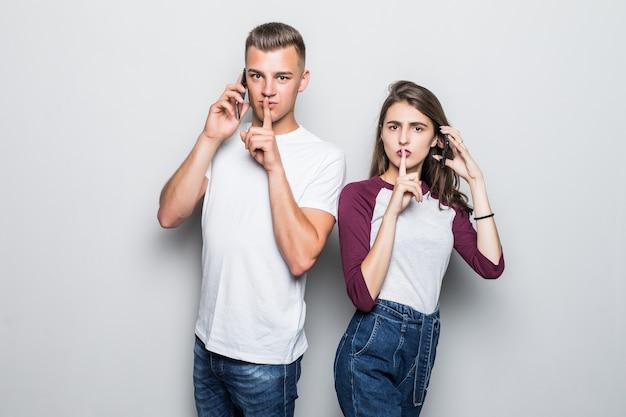 Довольно молодая красивая пара мальчик и девочка просят молчать во время телефонного звонка, изолированного на белом