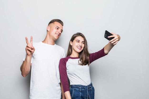 Bella giovane coppia bello ragazzo e ragazza che fanno selfie sul loro telefono isolato su bianco
