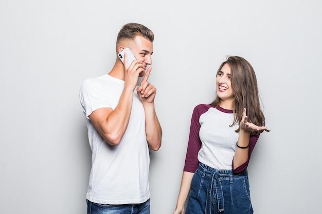 Il ragazzo abbastanza giovane delle coppie belle ha una conversazione segreta su pnone vicino alla sua ragazza isolata su bianco
