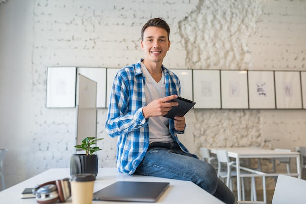 Довольно молодой красавец в рубашке chekered сидит на столе с помощью планшетного компьютера в коворкинге