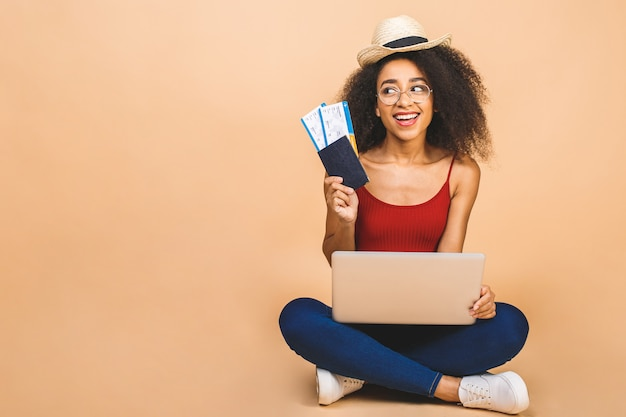 Pretty young happy black woman sitting on the floor with laptop and plane tickets over beige.