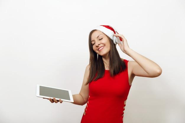 Довольно молодая счастливая женщина в красном платье и рождественская шляпа слушает музыку на наушниках, держа таблетку на белом фоне. изолированный гаджет девушки санты. новый год праздник 2018. копирование пространства рекламы.