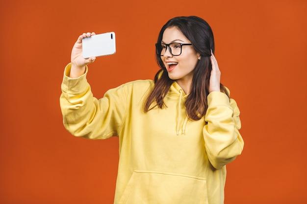 Довольно молодая счастливая женщина делая selfie на smartphone изолированном над оранжевой предпосылкой. использование телефона для селфи.