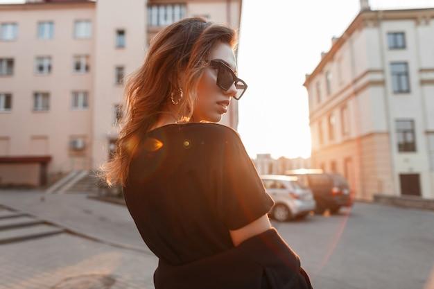 코트에 검은 색 tshirt의 유행 선글라스에 꽤 젊은 힙 스터 여자는 도시를 여행합니다