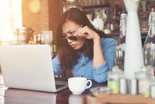 彼女のラップトップ、loとカフェに座ってかなり若いヒップな女