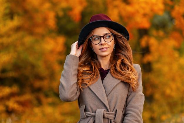 エレガントなコートを着たファッショナブルなメガネでヴィンテージの帽子をかぶったスタイリッシュな髪型のかなり若い流行に敏感な女性が秋の公園を歩きます。魅力的な女の子モデルは森の中を散歩を楽しんでいます。