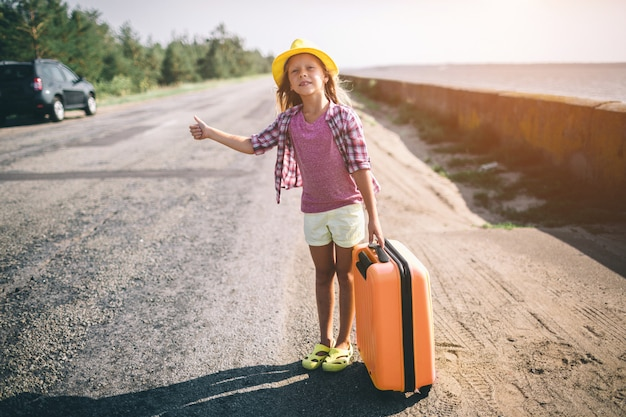 Pretty young hitchhiking little girl along a road