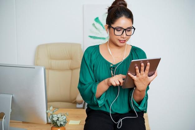 タブレットコンピューターでプレゼンテーションを見ているときに彼女のオフィスの机に寄りかかってイヤホンを身に着けているかなり若いインドのビジネス女性