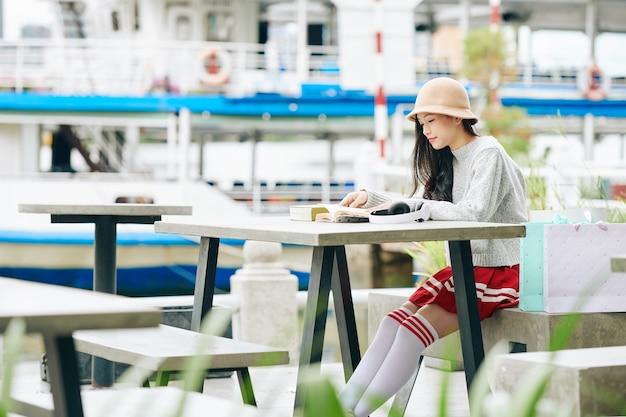 川岸のテーブルに座って本を読んで制服を着たかなり若い韓国の女の子