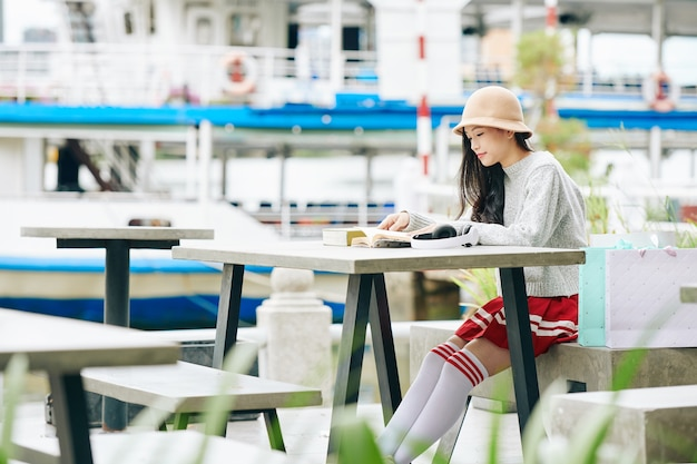 Pretty young korean girl in school uniform sitting at table by river bank and reading book