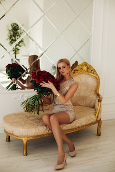 Pretty young lady in dress sitting on sofa and holding bouquet of roses