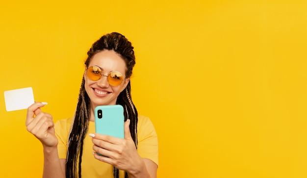 Довольно молодая дама в яркой одежде смотрит камеру и позирует с синим телефоном и кредитной картой.